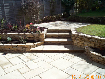 Dry stone walls have been used to create a new patio area around a new conservatory