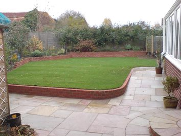A sloping garden that has been levelled with a retaining wall to provide a level lawn. A new patio has also updated the previously tired garden