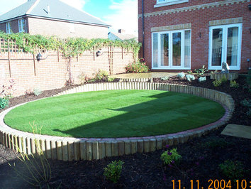 A gently sloping garden terraced to provide a level lawn area, new patio, water feature and planting