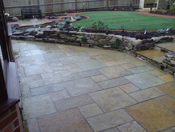 A garden rebuilt following the customers original design many years previously. The stone for the retaining walls was recovered from the original construction.