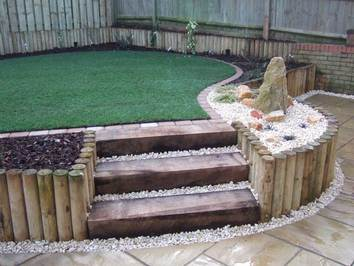 A sloping garden that has been terraced to provide a level lawn, patio planting areas and a water feature.