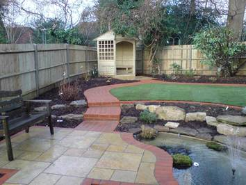 A new seating area alongside an existing pond with steps leading to a new gazebo.