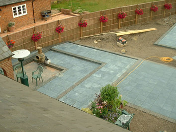 Part of a large scheme in a new garden involving steps up to two paved areas, new fencing, a hot tub, large summerhouse, lawns and planting.