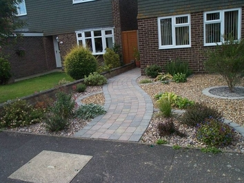A low maintenance front garden with a curved path and planting areas set amongst gravels.
