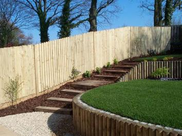 A sloping garden that has been terraced using timber to create an area of level lawn. Sleeper steps provide access to the higher level.