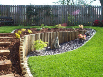 A loping garden contoured using timber posts to create a more useable lawn area