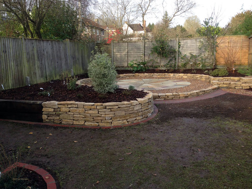 An area of an existing garden re-developed to include a paved circle using Indian sandstone slabs, a purbeck stone raised bed, a brick path and brick edges to the lawn and planted borders mulched with bark and weed supressing sheet to keep maintenance to a minimum