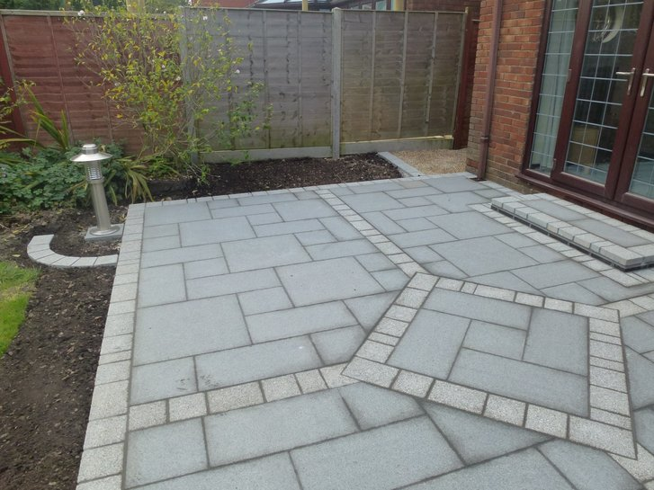 A new patio built with Chinese Granite paving slabs and Argent light paviours to add detail