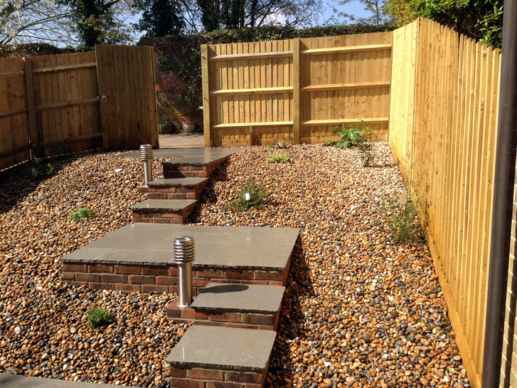 A complete garden makeover including fencing, patio, steps up to rear gate, lighting, planting and gravel for a low maintenance garden