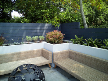 Part of a seating area surrounded with raised beds and screening from a parking area