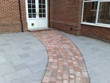 A new granite patio with a contrasting curver path leading to the rest of the garden.