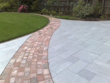 Another view of a curved path leading through a granit patio to the garden beyond.
